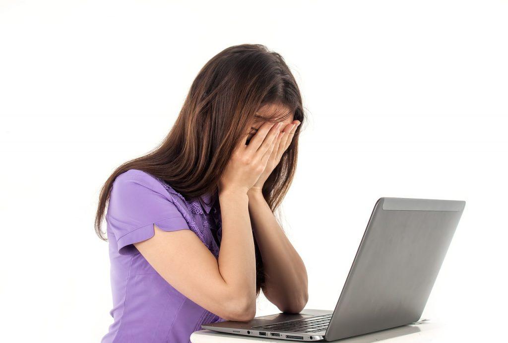 kobieta siedzi przed komputerem z twarzą w dłoniach